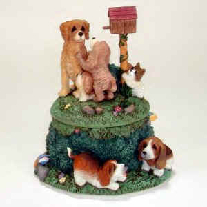 Lou Rankin's musical figurines have many puppies playing on top and around the music box.